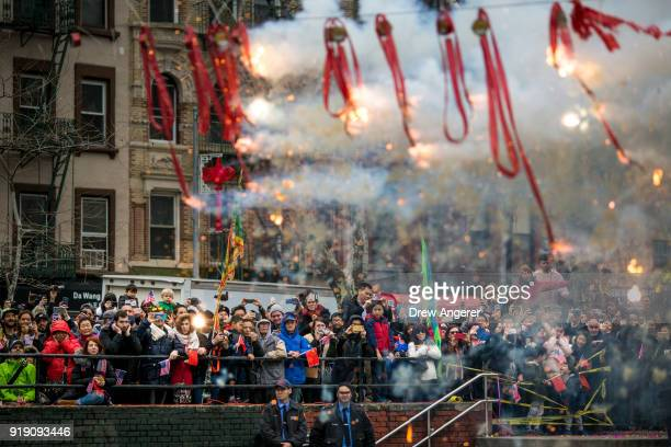 People watch the firecracker ceremony at a cultural festival to mark the first day of the Lunar New Year in Chinatown neighborhood in Manhattan,...