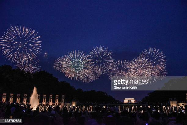 People watch the fireworks display on the National Mall during Fourth of July festivities on July 4 2019 in Washington DC President Trump is holding...
