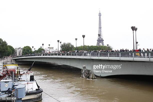 People watch the flood water level of Seine river from Pont de l'Alma bridge with the partially submerged statue 'Le Zouave' on June 03 2016 in Paris...