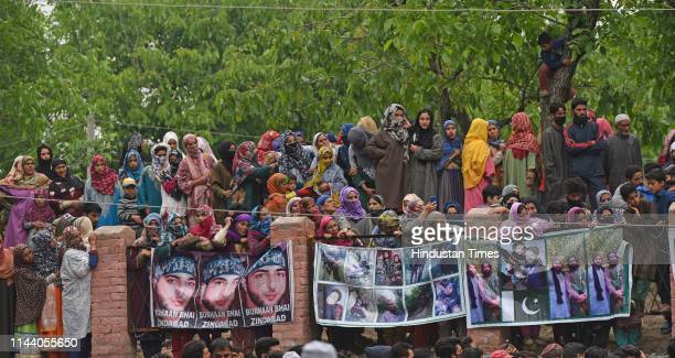 People watch the funeral procession of a Jaish-e-Mohammed militant Naseer Pandith, at Karimabad on May 16, 2019 in Pulwama, India. Three militants,...