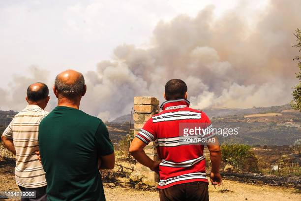 People watch the hill burning near the Oristano freeway in south west Sardinia.