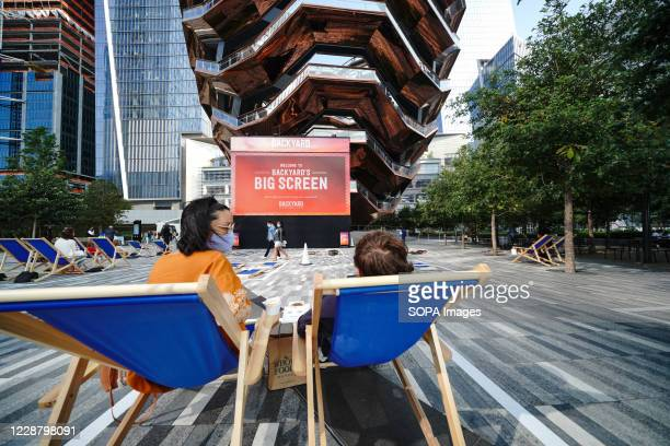 People watch the Hudson Yards Backyard Big Screen curated in partnership with Tribeca Film Festival as patrons enjoy socially distant pods with...