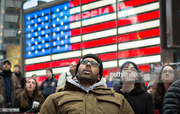 TOPSHOT People watch the inauguration of Donald Trump on a screen in Times Square on January 20 2017 in New York Barack Obama and Donald Trump...