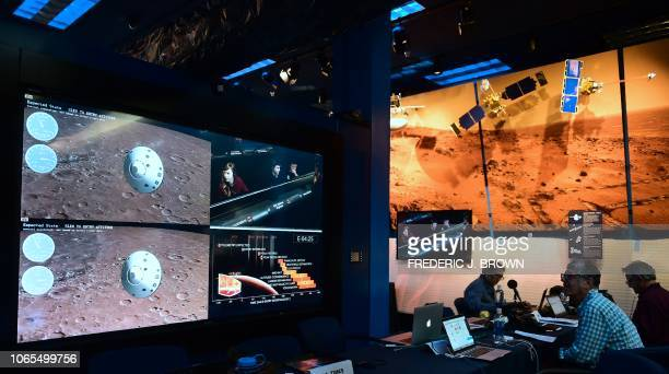 People watch the landing of NASA's InSight spacecraft on the planet Mars on television screens at NASA's Jet Propulsion Laboratory in Pasadena...