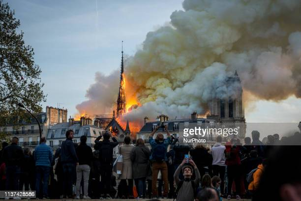 People watch the landmark NotreDame Cathedral burning in central Paris on April 15 2019 A fire broke out at the landmark NotreDame Cathedral in...