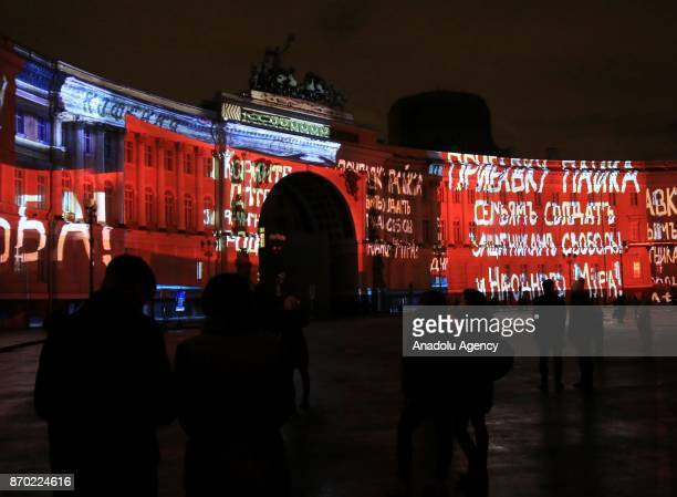People watch the light show 1917 projected on General Staff building to mark the 100th anniversary of the Bolshevik Revolution in Saint Petersburg...