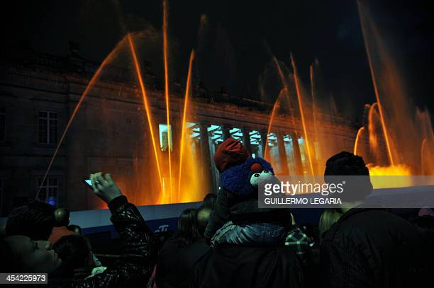 People watch the lights and water show at the main square of Bogota on December 7 2013 AFP PHOTO/Guillermo Legaria