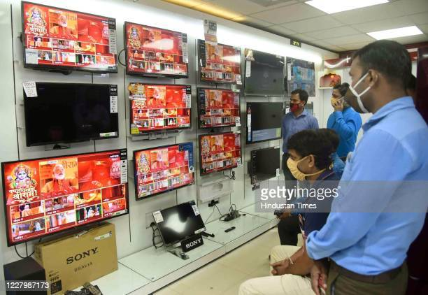 People watch the live telecast of the Bhumi Pujan ceremony at an electronic store, on August 5, 2020 in Patna, India.