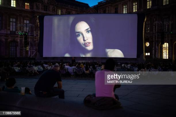 People watch the movie La Reine Margot at the Louvre Museum during the first of eight screenings of the outdoor cinema Cinema Paradiso Louvre in...