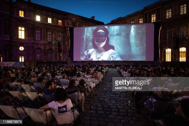 """People watch the movie """"La Reine Margot"""" at the Louvre Museum during the first of eight screenings of the outdoor cinema """"Cinema Paradiso Louvre"""" in..."""