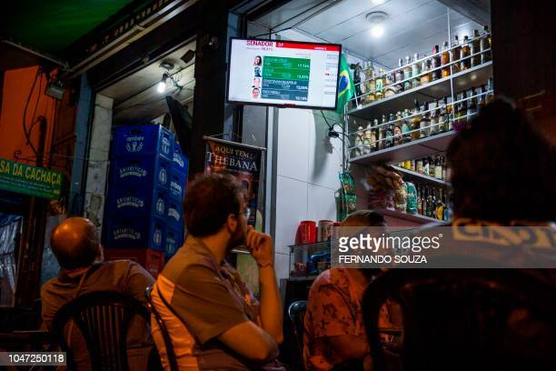 People watch the news coverage of the 2018 Brazilian general election at a bar of Lapa neighborhood in Rio de Janeiro Brazil on October 07 2018...