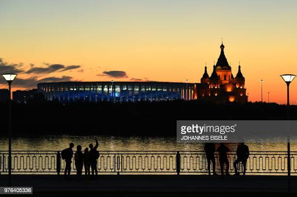 People watch the Nizhny Novgorod stadium situated behind the cathedral of Alexandr Nevskiy in the city of Nizhny Novgorod during the Russia 2018...