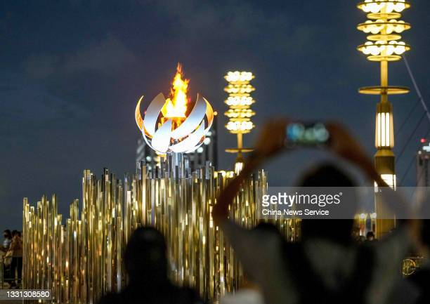 People watch the Olympic flame burning on the cauldron at Ariake Yume-no-Ohashi Bridge on day six of the Tokyo 2020 Olympic Games on July 29, 2021 in...