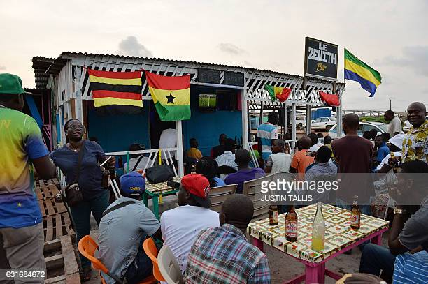 People watch the opening game of the 2017 Africa Cup of Nations football tournament between Gabon and GuineaBissau at a bar in PortGentil on January...