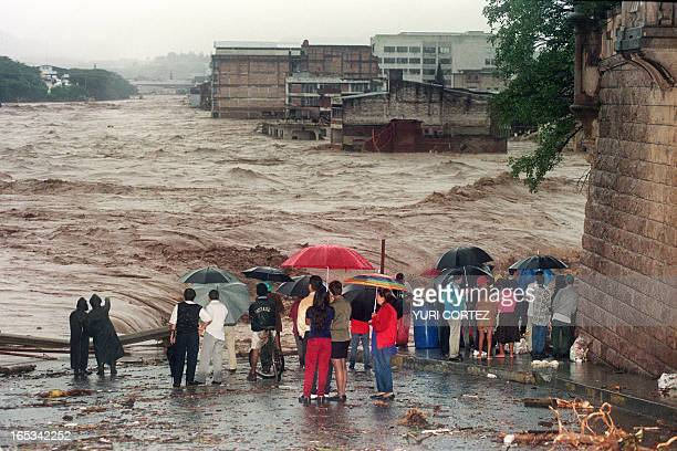 People watch the overflowing waters of the Choluteca River 31 October 1998 in Tegucigalpa Honduras Heavy rains and severe flooding continued 31...