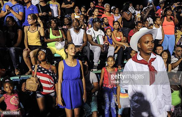 People watch the parade to celebrate the 500th anniversary of the foundation of Santiago de Cuba and the 62nd anniversary of the guerrilla assault on...