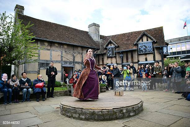 People watch the performance of excerts of a Shakespeare play in the grounds of the birthplace of William Shakespeare during events marking 400 years...