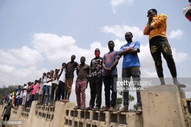 TOPSHOT People watch the remains of Nigerias Chief of Staff Abba Kyari being buried at the Gudu Cemetery in Abuja on april 18 2020 Abba Kyari the...