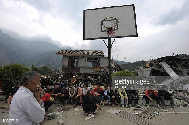 People watch the rescue on their children at a collapsed elementary school in Yingxiu of Wenchuan county after a quake with a magnitude of 78 rocked...