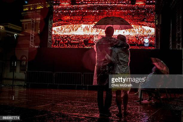 People watch the Rio 2016 Olympics closing ceremony in the rain at the Olympic Boulevard live site on August 21 2016 in Rio de Janeiro Brazil