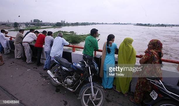 People watch the rising waters of the Yamuna river at the Geeta Colony in New Delhi on September 11 2010