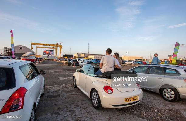 People watch the romantic musical film Grease from their cars at a temporary drive in cinema situated by the iconic Harland and Wolff cranes at...