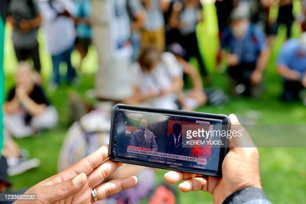 People watch the sentencing hearing of former Minneapolis Police officer Derek Chauvin outside the Hennepin County Government Center on June 25, 2021...