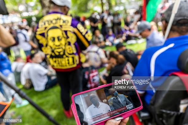 People watch the sentencing hearing of former Minneapolis Police officer Derek Chauvin on a smartphone, outside the Hennepin County Government Center...