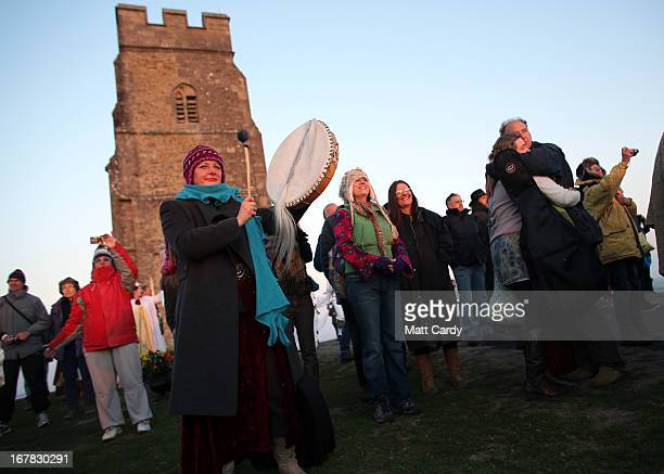 People watch the sun rise as they join in a Beltane dawn celebration service in front of St Michael's Tower on Glastonbury Tor on May 1 2013 in...