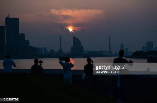People watch the sun rise over the Huangpu river in Shanghai on August 8 2018