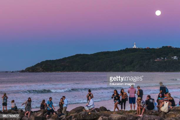 People watch the sun set and full moon rise at Byron bay New South Wales Australia