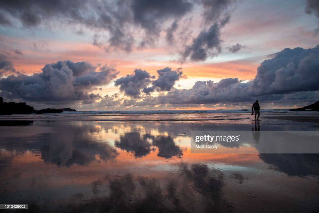 People watch the sun set at Porth beach on the first day of the annual Boardmasters festival that is taking place in Newquay on August 8, 2018 in Cornwall, England. Since 1981, the Boardmasters surfing competition has been held in Newquay and is now part of a larger five-day surf, skate and music festival becoming an integral part of the continually popular British surf scene, growing from humble beginnings, to one of the biggest events on the British surfing calendar. It now attracts professional surfers from across the globe to compete on the Cornish beach that is seen by many as the birthplace of modern British surfing..