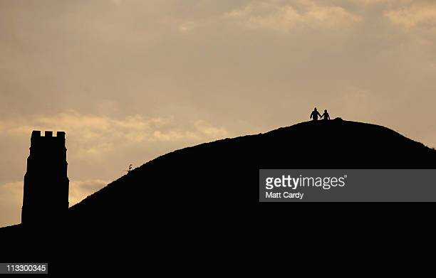 People watch the sunrise as druids and pagans conduct a May Day dawn celebration service in front of St Michael's Tower on Glastonbury Tor on May 1...