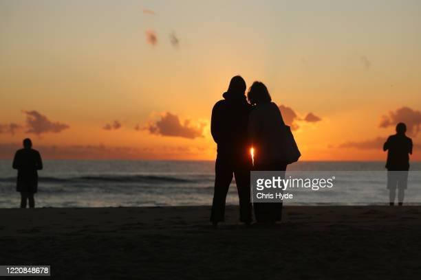 People watch the sunrise on Currumbin Beach to commemorate Anzac Day on April 25 2020 in Gold Coast Australia Traditional Anzac Day ceremonies have...