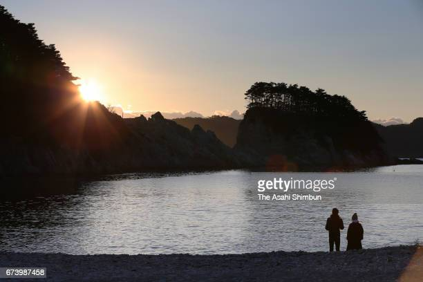 People watch the sunrise over at Jodogahama Beach on the sixth anniversary of the Great East Japan Earthquake and following tsunami on March 11 2017...