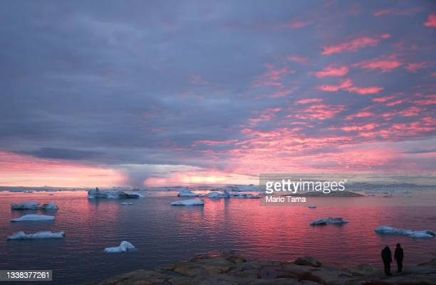 People watch the sunset as rain falls in the distance beyond floating ice and icebergs in Disko Bay on September 04, 2021 in Ilulissat, Greenland....