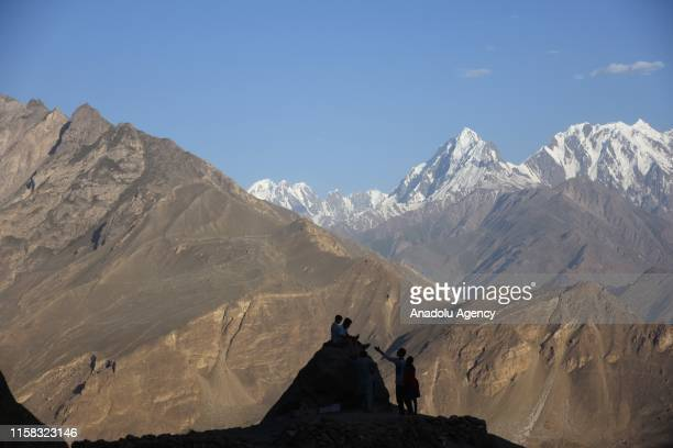 People watch the sunset at the summit of a mountain on the Karimabad Region where a number of summits meet and host historical Baltit Fort also known...