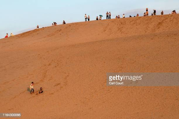 People watch the sunset from Tottori Sand Dunes on August 26, 2019 in Tottori, Japan. The Tottori Sand Dunes form the only large dune system in Japan...