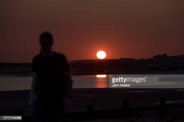 People watch the sunset on Chalkwell beach on September 13, 2020 in Southend on Sea, England. Parts of the UK are expected to hit 29 degrees celsius...
