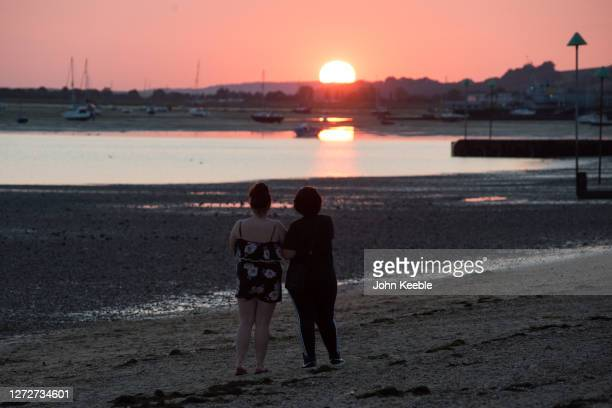 People watch the sunset on Chalkwell beach on September 13 2020 in Southend on Sea England Parts of the UK are expected to hit 29 degrees celsius as...