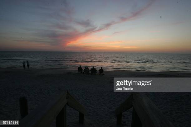 People watch the sunset on the beach in a city that a recent survey declared the most overvalued housing market in the US March 16 2006 in Naples...