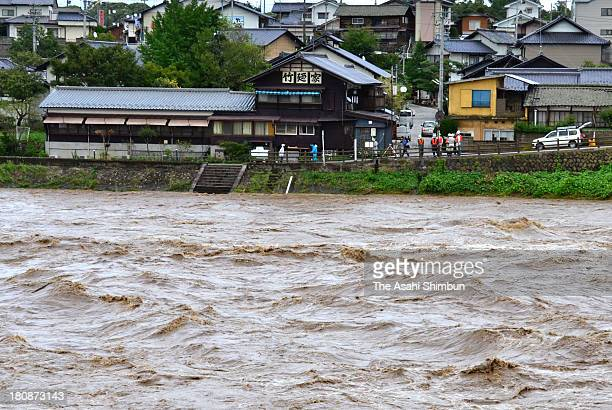 People watch the swollen Chikuma River triggered by typhoon ManYi approaching on September 16 2013 in Saku Nagano Japan The storm hit land near...