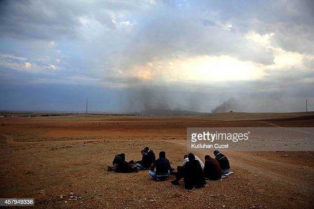 People watch the Syrian town of Kobani from a hill near the Mursitpinar border crossing on October 27, 2014 at the Turkish-Syrian border in the...