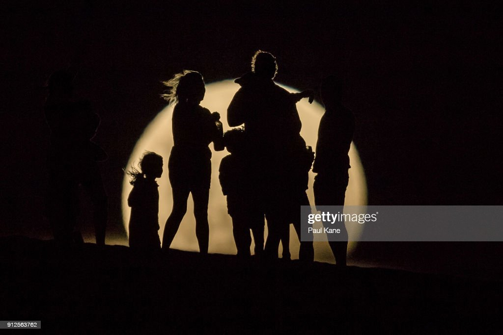 People watch the the Super moon rising in the sand dunes on January 31, 2018 in Lancelin, Australia. Last seen from Australia in December 1983, a Super Blue Blood Moon is the result of three lunar phenomena happening all at once. Not only is it the second full moon in January, but the moon will also be close to its nearest point to Earth on its orbit, and be totally eclipsed by the Earth's shadow.