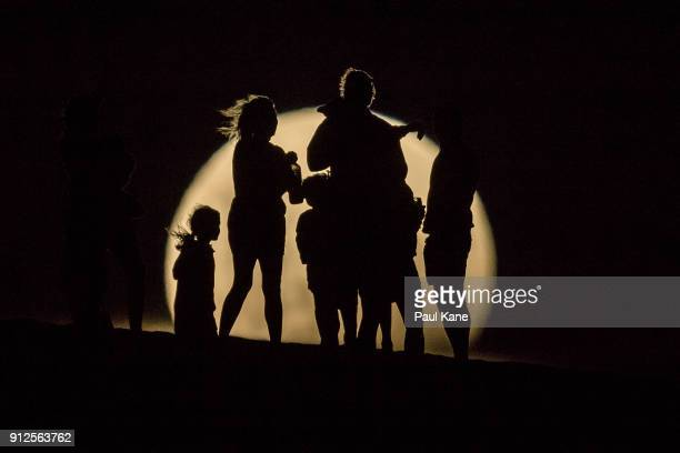 People watch the the Super moon rising in the sand dunes on January 31 2018 in Lancelin Australia Last seen from Australia in December 1983 a Super...