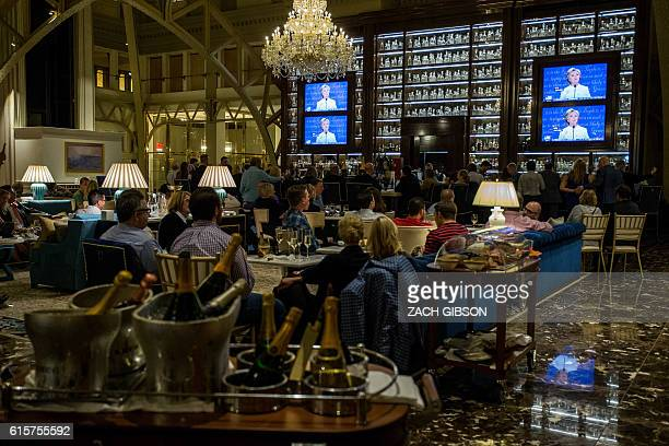 People watch the third presidential debate between presidential debate between US Democratic presidential candidate Hillary Clinton and US Republican...