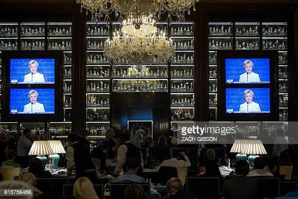 TOPSHOT People watch the third presidential debate between presidential debate between US Democratic presidential candidate Hillary Clinton and US...