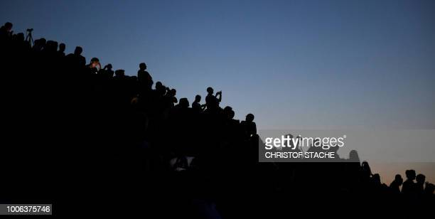 People watch the total lunar eclipse in the Olympic park in Munich southern Germany on July 27 2018 The longest blood moon eclipse this century began...
