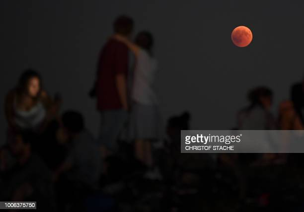 TOPSHOT People watch the total lunar eclipse in the Olympic park in Munich southern Germany on July 27 2018 The longest blood moon eclipse this...