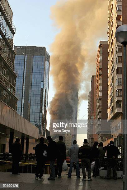 People watch the Windsor skyscraper smolder on February 13 2005 in Madrid Spain There are no reported civilian casualties after the blaze broke out...